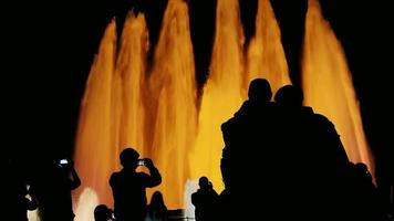 recognizable silhouettes of people in singing fountain in Barcelona. People watching the show, photographed fountain