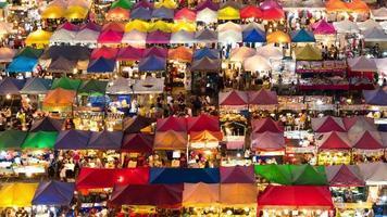 4k-uhd, pan di gente che compera nel mercato notturno colorato