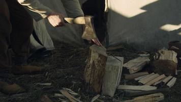 hombre cortando leña. vida de la población civil en el pueblo. Recreación medieval.