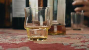 pessoas bebem álcool no terraço. homem colocou o copo curto na mesa. torcendo