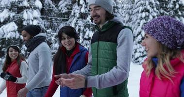 grupo de pessoas na floresta de neve de inverno caminhando sorrindo amigos conversando em um parque nevado
