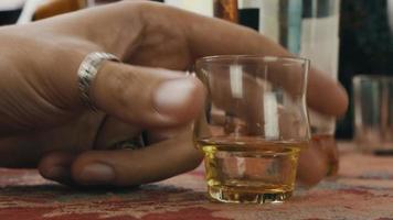 pessoas bebem álcool no terraço. homem colocou o copo curto na mesa. torcendo. garrafa