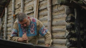vida de la población civil en el pueblo. vestido con ropa medieval, el hombre hace un barco. Recreación medieval.