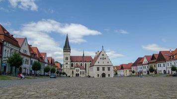 lapso de tiempo de personas y nubes en el centro histórico de bardejov en eslovaquia. hacer zoom en la iglesia