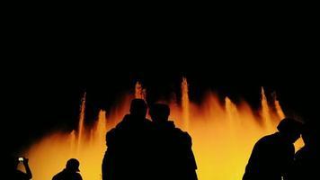 silhouette persone irriconoscibili nella fontana cantante. la fontana è illuminata magnificamente. barcellona: spagna - una popolare destinazione turistica video