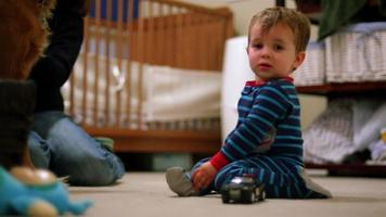adorável garotinho de pijama brincando com um carro de polícia de brinquedo no chão de seu quarto