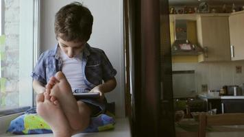 A cute little boy sits on a windowsill at home and touches a tablet PC