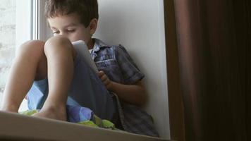 BOTTOM VIEW: A cute little boy uses a white tablet PC on a windowsill at home