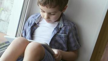 PORTRAIT: A cute little boy uses a white tablet PC on a windowsill at home