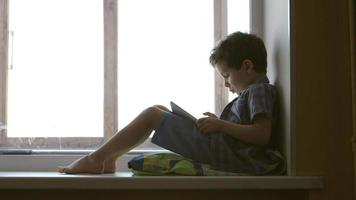 SIDE VIEW: A cute little boy uses a white tablet PC on a windowsill at home - middle shot