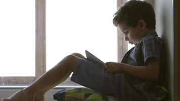 SIDE VIEW: A cute little boy uses a white tablet PC on a windowsill at home