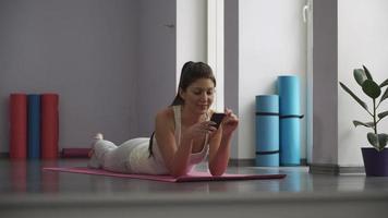 niña acostada en la estera de yoga y mirando el teléfono