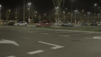4k: guida con auto al parcheggio di notte, vista laterale