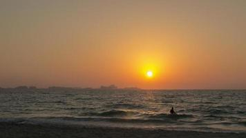 il sole tramonta all'orizzonte sulla spiaggia