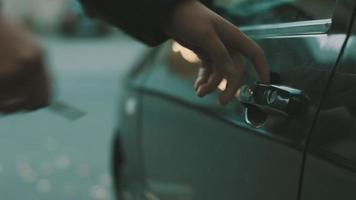 el hombre viene al auto, abre la puerta y se sienta adentro