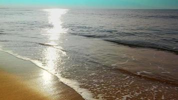 loop uniforme, areia de praia tropical, pegadas enquanto as pessoas caminham nas ondas