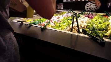 pessoas no bufê de saladas 4k