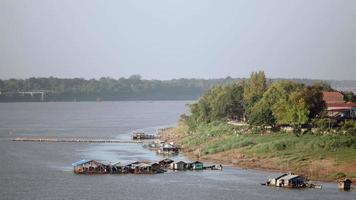 schwimmende Häuser am Flussufer und Menschen, die den Weg vom Pier in die Stadt hinaufgehen
