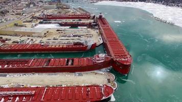 muchos grandes buques cargueros atracados en aguas cubiertas de hielo
