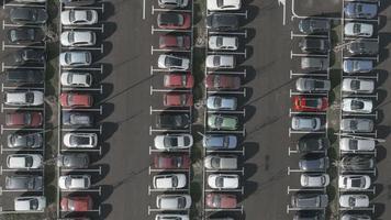 Aérea 4k: carro vermelho deixando estacionamentos cheios de carros video