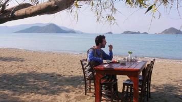 turista homem comendo lindo café da manhã na praia com fundo do mar majestoso