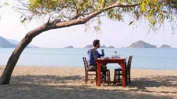 Touristenmann, der herrlichen Frühstücksstrand mit majestätischem Meereshintergrund isst