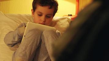Little boy lays in a bed and looks at a tablet PC