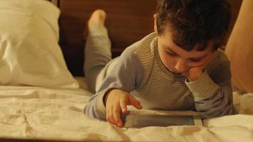Little boy lays in a bed and touches on a tablet PC at home