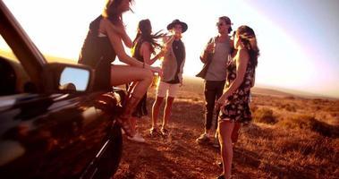 gruppo di amici in un tranquillo tramonto estivo festa vicino a una decappottabile