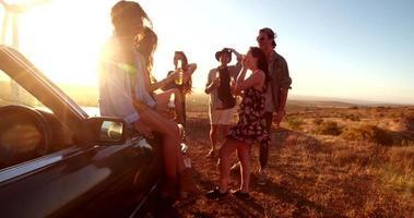 amici di viaggio su strada che fanno festa all'aperto in una sera d'estate