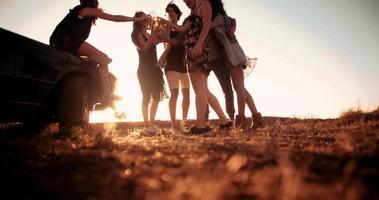 Friends enjoying a peaceful summer sunset partying near a convertible