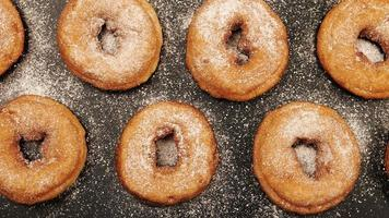 TOP VIEW: Dolly shot of a rows of doughnuts with sugar powder on the black desk