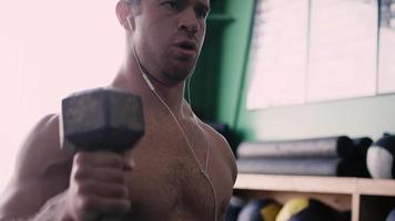 Ein fitter junger Mann, der in einem kleinen Fitnessstudio Hanteln hebt, während er Musik hört