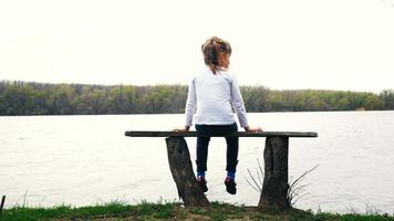 menina bonita sentada no banco perto do rio video