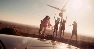 Amigos con bandera americana visitando parque eólico en viaje por carretera video