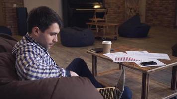 uomo attraente in una camicia a quadri seduto a riposo, guardando il monitor e bere caffè