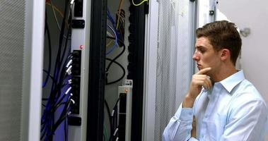técnico olhando para o armário do servidor aberto