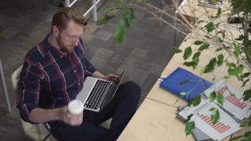 Hombre barbudo tomando café y navegando por internet mientras se relaja en una silla