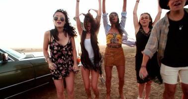 Adolescentes celebrando con confeti de colores en un viaje por carretera de verano fuera video