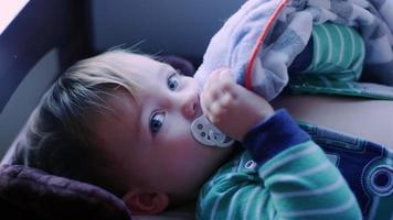 adorável menino deitado em um trocador com uma chupeta na boca, sorrindo