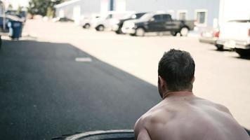 Un hombre joven en forma haciendo un tirón de neumático fuera de un pequeño gimnasio video