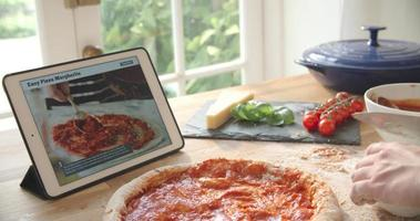 Person Following Pizza Recipe Using App On Digital Tablet video