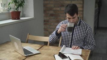 no café, o homem sentado à mesa lendo uma revista e bebendo café video