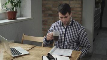 homem atraente tomando café e lendo o jornal, está na mesa, telefone e laptop video