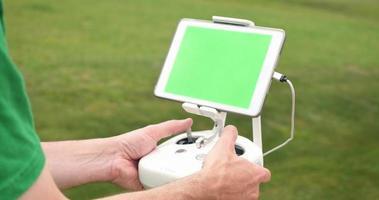 homem usa controlador rc para uav drone fora do tablet com tela verde
