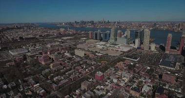 Antennen fliegen über Gebäude in Richtung Hochhäuser mit Manhattan in der Ferne