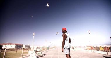 cara afro casualmente praticando longboard em uma passarela na praia