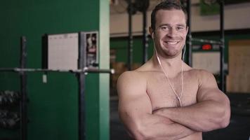ritratto di un giovane uomo in forma con le cuffie incrociando le braccia e sorridente in una piccola palestra