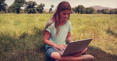 bella bionda rilassante nel parco con il suo laptop