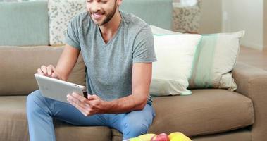 jovem feliz usando seu tablet